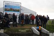 Zoontje Tom van agrariër Nico Neppelenbroek trekt samen met bestuurder Henk Oegema van Waterschap Drents Overijsselse Delta (links) en gedeputeerde Cees Bijl van de provincie Drenthe (midden) de schuif omhoog. Rechts Nico Neppelenbroek.